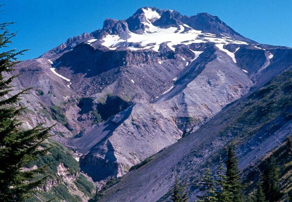 A high mountain summit laced with snow, draining down through rocky slopes.