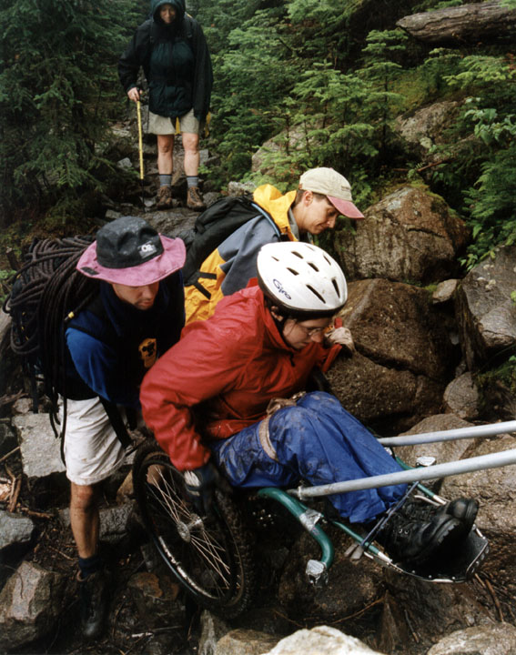 A visitor in an all-terrain wheelchair is assisted over a rough section of forest trail by two friends.