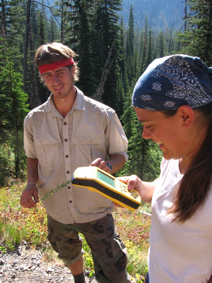 A volunteer utilizes a GPS unit while another volunteer watches. This photo was taken during University of Montana summer 2007 volunteer weed inventory study.
