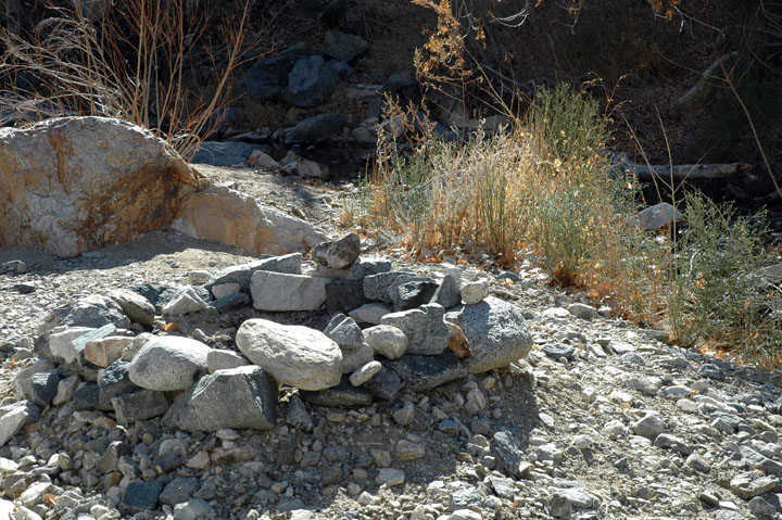 An old fire ring composed of many small rocks, sitting along the edge of a campsite near tall grass.