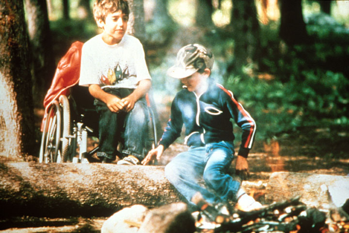 A young boy in a wheelchair, sits next to a campfire, while his friend sits on a log.