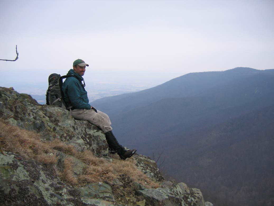 A lone backpacker sitting high on a rocky ledge, overlooking a forested valley far below.
