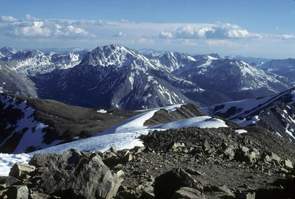 This shot of the Collegiate Peaks from another peak in the range, depicts the snow-capped, rocky peaks while clouds scuttle in the background.