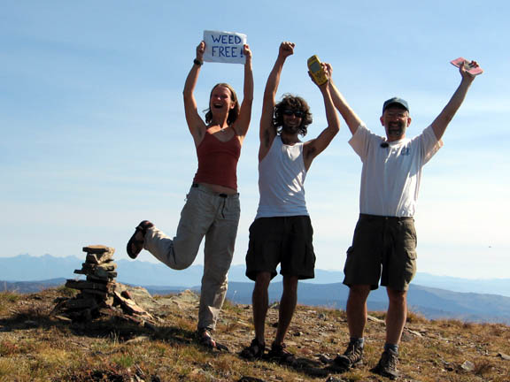 Three college-age volunteers join hands and cheer after a day of removing invasive plants from Stuart Peak. One student holds up a small sign that reads 'Weed Free'.
