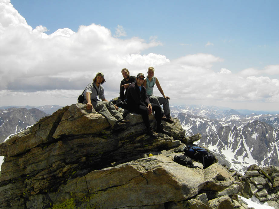 Four men sit on a large boulder at the summit of a peak, overlooking a seemingly endless landscape of advancing peaks in the distance.