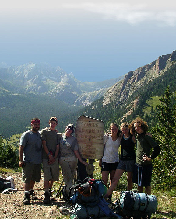 A small group of backpackers standing next to a signpost high in the mountains. Behind them a green valley stretches off into the haze, bordered by rocky mountains.