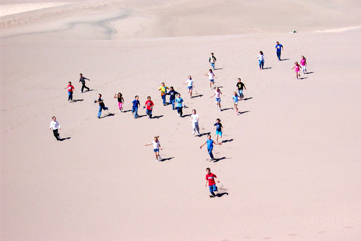 Children running down a tall sand dune appear brightly colored against the pale pink dune sand.