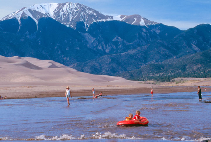 Young children on a bright red innertube play in the water along the beach with several adults in the background. Golden sand dunes and tall snowcapped mountain rise in the distance.