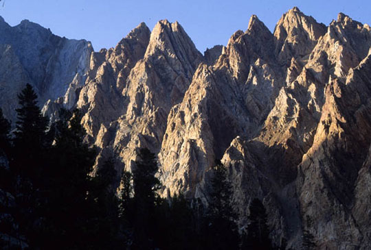 A sunset illuminates the peaks of Mt. Emerson. These peaks jut and rise, towering just below the sky.