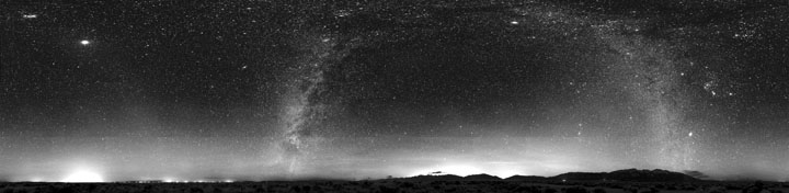 A black and white panoramic image of the night sky showing the stars and constellations with the light pollution from urban areas leaking up from the horizon.