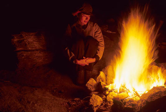 A female hiker, her face illuminated by fire light, enjoys the tranquility of a campfire.