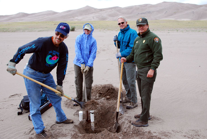 Several rangers and volunteers use shovels to remove an old monitoring well from the sand.