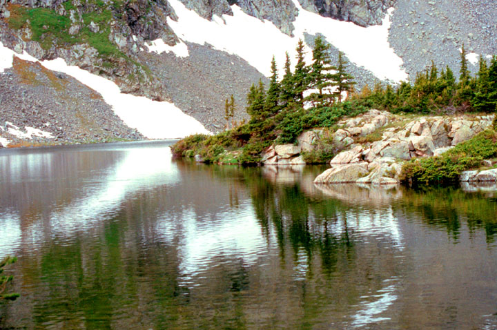 Small trees and patches of snow dot a rocky face and reflect off the surface of an alpine lake in the foreground.