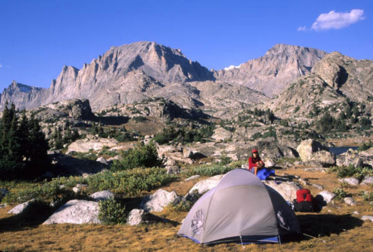 A backpacker sets up camp near Island Lake, in the Wind River Range. The sun shines out from a clear sky as the mountains in the background cast shadows on the rocky landscape.