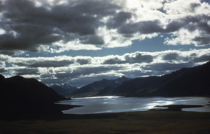 A moody image of a large silver lake in mottled shadow, sparse rays of sunlight filtering down into the surrounding valley through the broken clouds above.