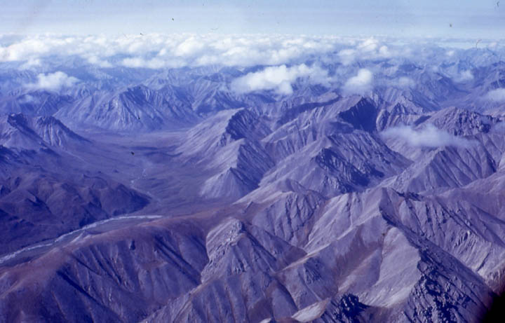 An aerial view looking down over an endless landscape of mountain peaks dotted with puffy white clouds.