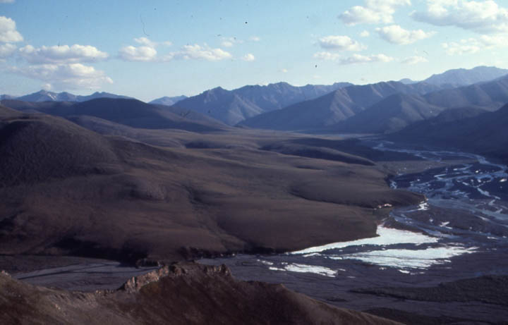 A barren landscape of a braided river flowing along rolling hills, with jagged mountains in the background.