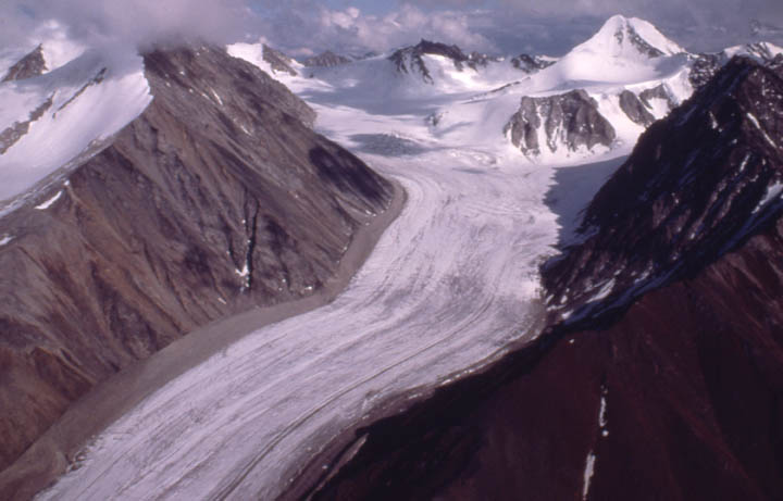 A massive glacier sweeping down a valley from a high ice field, surrounded by jagged peaks of black rock.