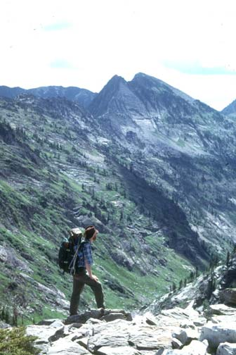 A lone backpacker, standing high on a rocky slope, overlooking an alpine valley below a rocky peak beyond.