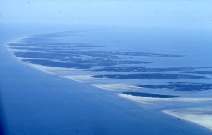 An aerial view of a small sandy barrier island chain, sweeping away into the hazy blue horizon.