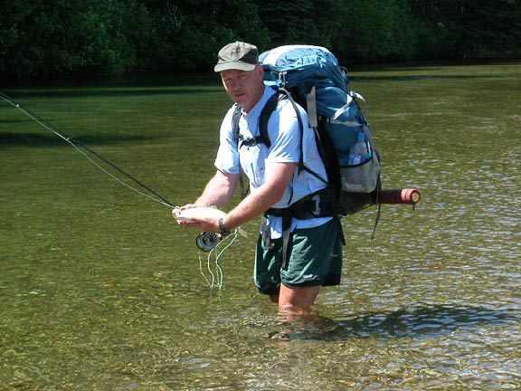A close-up of a man with a large backpack, standing knee-deep in the green water, holding a fish in his hands.