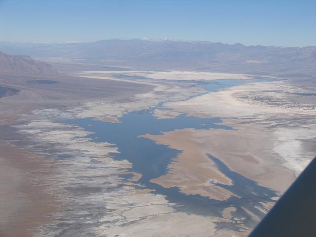 An aerial shot of a large lake spreading out across Death Valley Wilderness.