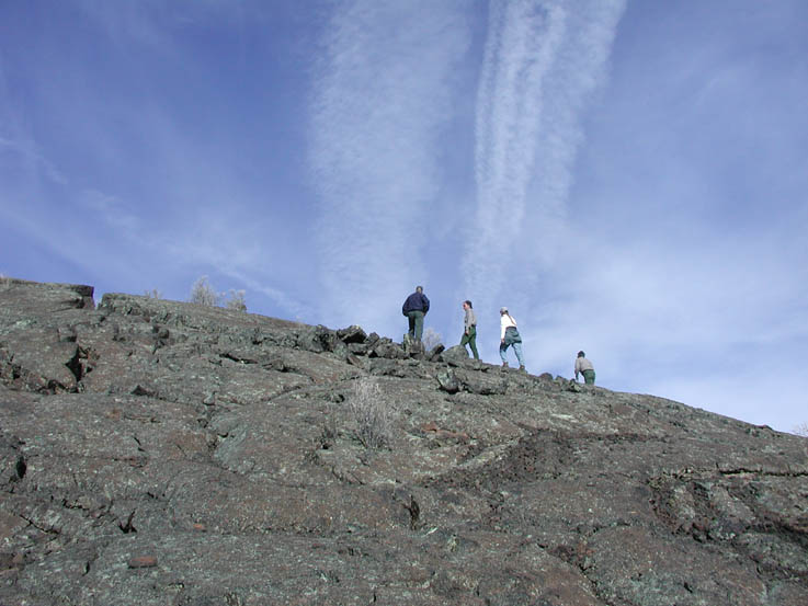 Four hikers climbing a barren rock slope, under a blue sky laced with clouds and contrails.