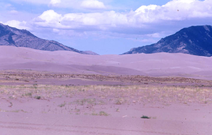 Low mountains rise from the far side of an open valley, filled with gray sand dunes.
