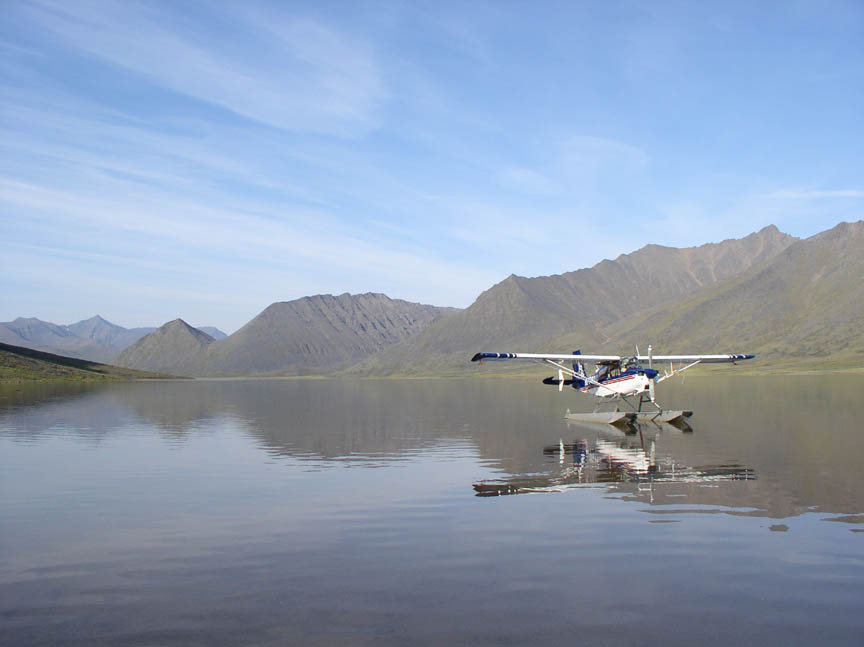 A floatplane floating near shore, on a tranquil lake. The glassy water reflecting the blue sky over the jagged mountains surrounding.