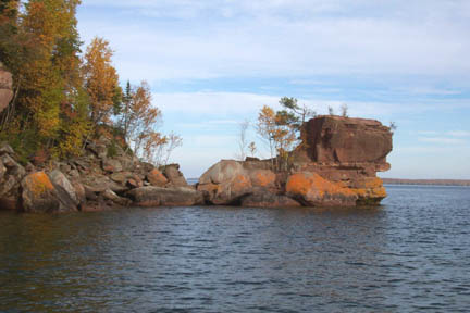 A small rock outcropping sticking out into the water, covered in orange lichen and topped by trees in bright yellow and orange autumn color.