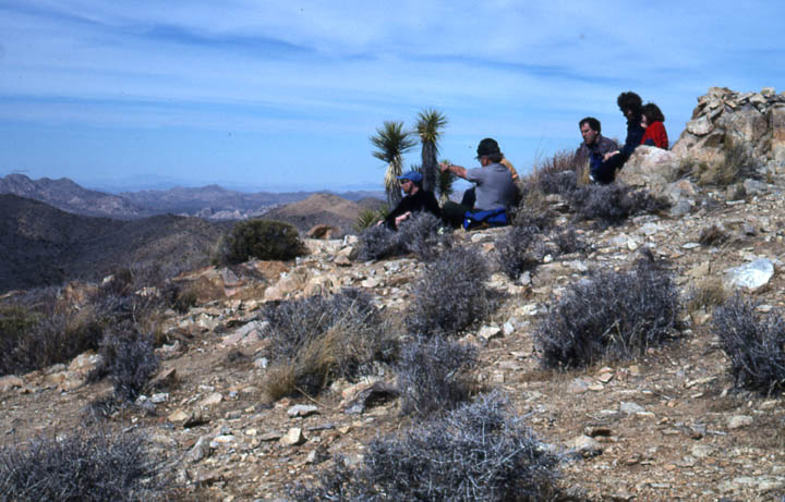 A small group of hikers relaxing on the rocky ground, overlooking a desert landscape in the valley below.