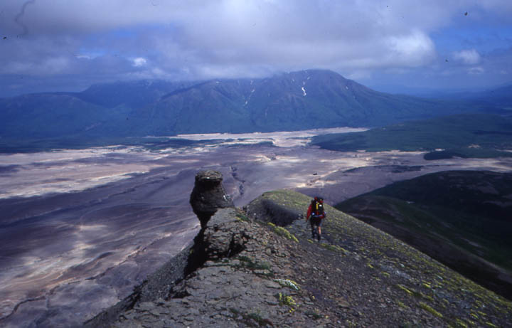 A lone hiker navigating a knife ridge, high above a wide river valley below, bordered by steep mountains covered in high clouds.