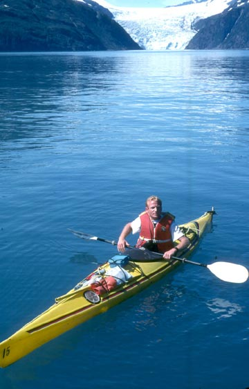 A blonde man in a sea kayak floats in a fjord with a glacier in the background.