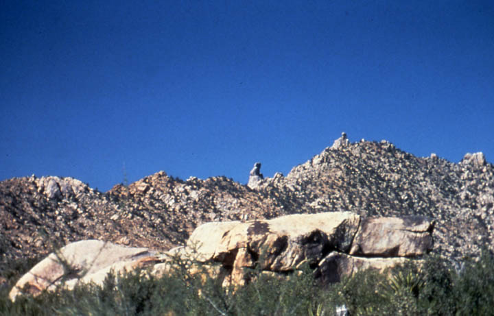 An empty blue sky over a rocky desert ridge, topped by rock pinnacles, and dotted with green brush.