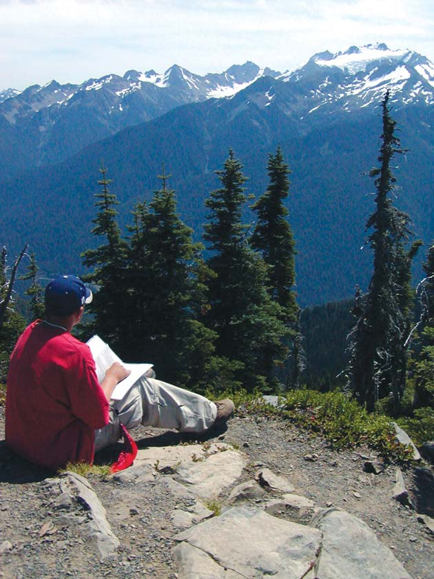 A man in a red jacket sitting high on a point, overlooking a deep forest valley below, rising to snowcapped peaks across.