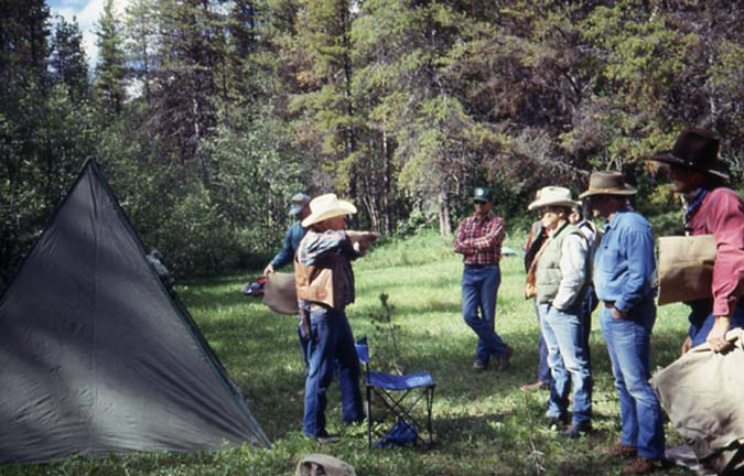 Several people in cowboy hats, gathered in a small clearing near a tent.
