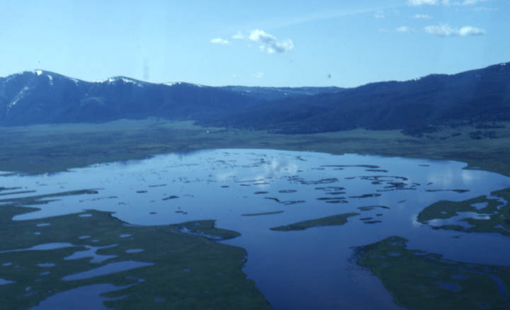 A large basin ringed by low mountains, surrounding a marshy lake dotted with small islands.
