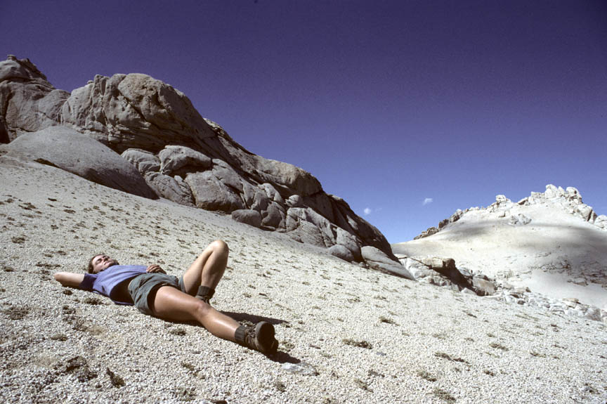 A person relaxing on a smooth slope, rock outcroppings rise above, against a deep blue sky.