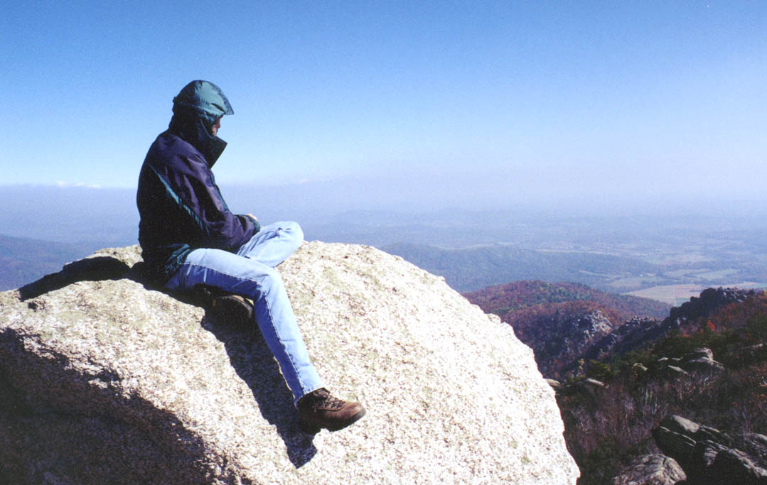 A person in a blue jacket sitting on a large granite boulder, overlooking a massive valley far below, stretching off into the hazy distance.