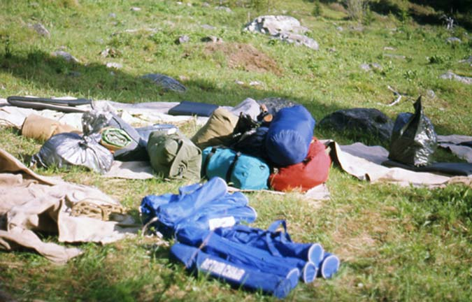 A pile of equipment in red, blue, and brown sacks, set in a pile on the green grass.