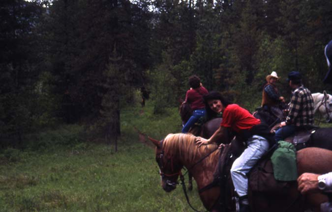 A woman in a red shirt on horseback, with several other people on horseback in the background.