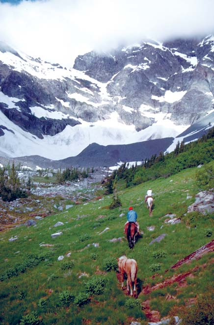 Three people on horseback, traveling through a lush alpine meadow towards the head of a high valley with massive rocky faces draped in hanging glaciers and laced with cloud.