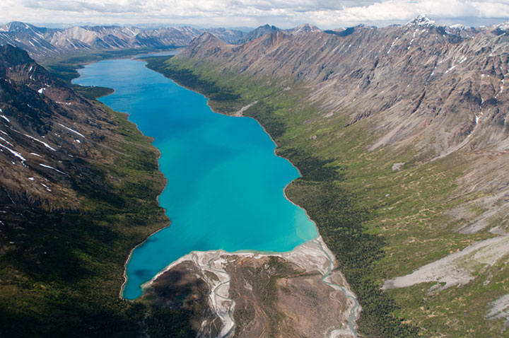 An aerial view of a large lake at the bottom of a steep valley
