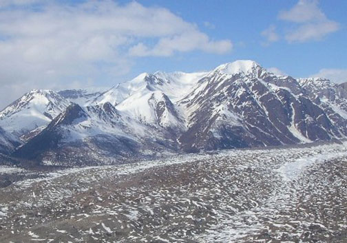 A massive glacier covered in mottled gray dirt, flowing past the base of a high snowcapped peak.
