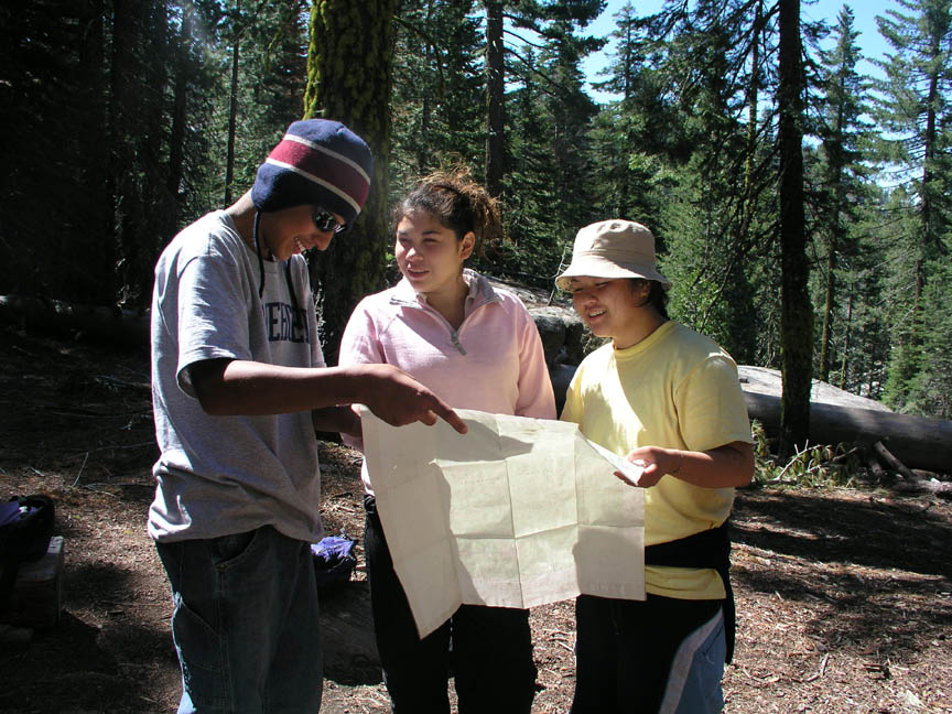 Three young people standing together along a forest trail, studying a map.