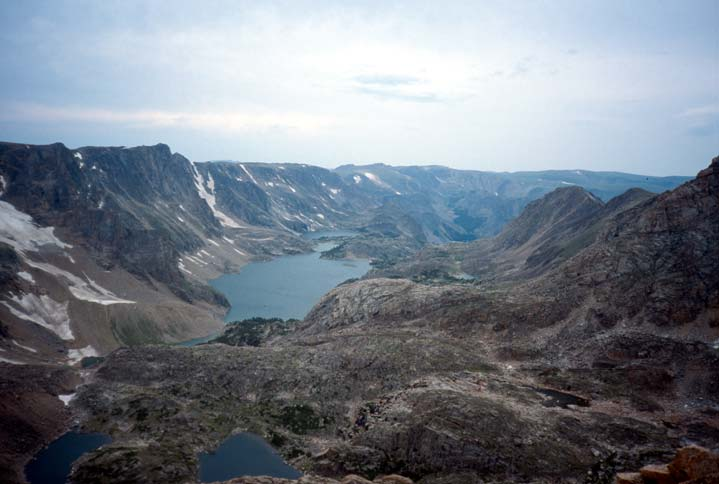 Viewing down over a high alpine bowl surrounded by rocky cliffs, two small ponds and a lake lie at the base, surrounded by barren rock.