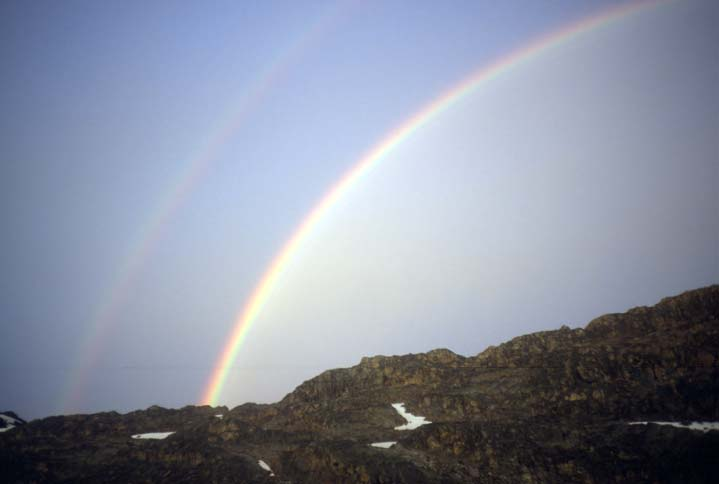 A brilliant double-rainbow against a gray sky, rising high over a ridge of black rock.