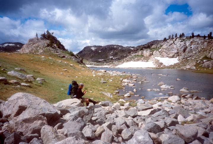 A lone hiker sitting on a pile of boulders, along the edge of a small alpine pond, surrounded by open grass and small rock faces.