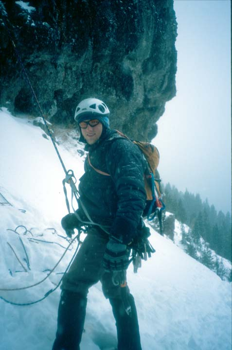 An ice climber in full gear, standing on a snow-covered slope at the base of a rock face.