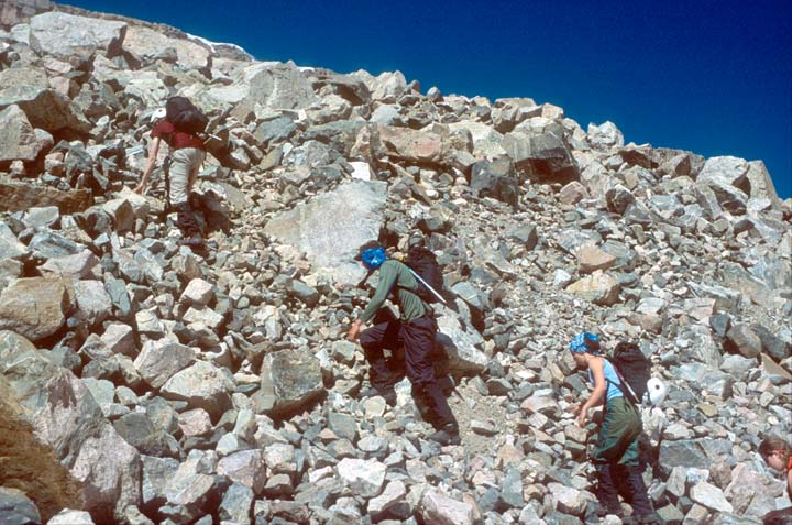 Three climbers ascending a steep moraine of jumbled rocks and boulders.